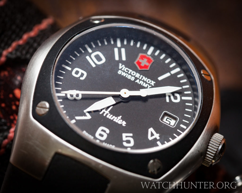On the front, a plastic bezel is attached with 4 screws and frames the dial. Mach 1 version shown.